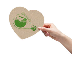 Hand picking brown paper heart and ecology sketch