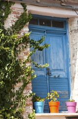 Blue wooden door and colorful flowerpots of stone house