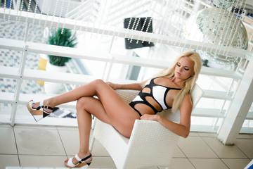 Девушка блондинка сидит на стуле