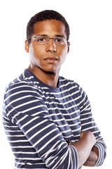 Serious dark-skinned young man with glasses and arms crossed