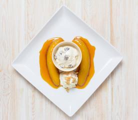 flambe banana with ice cream on wood table