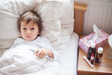 Fototapety Sick child boy lying in bed with a fever