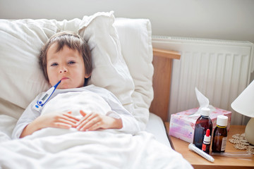 Sick child boy lying in bed with a fever