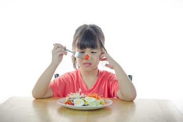 Cute Asian girl refusing to eat vegetable
