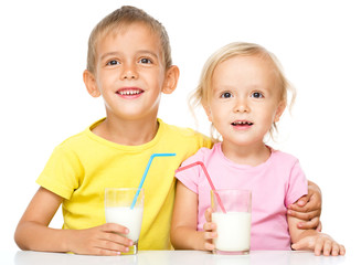 Cute little girl and boy are drinking milk