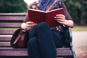 Young woman reading on park bench