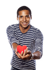 dark-skinned young man holding an object in heart shape