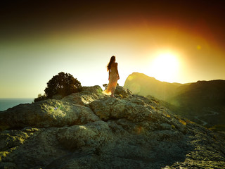 Woman silhouette at sunset in mountains