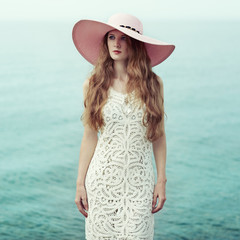 Beautiful woman in hat on the sea