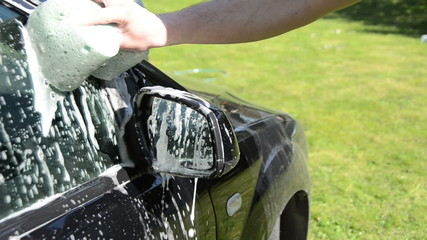 Close-up of man hand cleaning washing his car