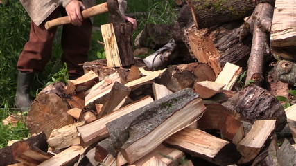 close up of hand chop with axe thick wood near woodpile