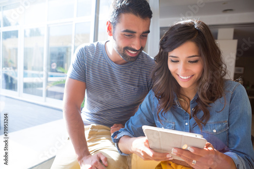 Couple using tablet with sunbeams and lens flare - 70953264