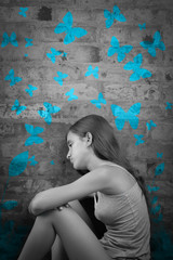 Sad teenage girl with blue butterflies painted on a wall