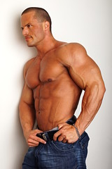 Handsome muscular man standing poses on the wall