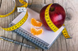 Measuring tape wrapped around a apple weight loss photo - 70954867