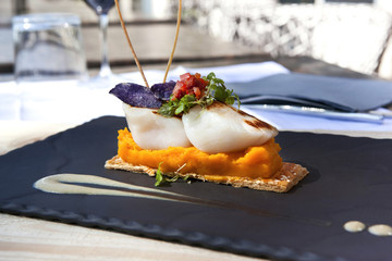 Saint-Jacques scallops, carrots puree and biscuit on a slate