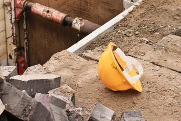 Ein gelber Schutzhelm liegt neben einer Baugrube