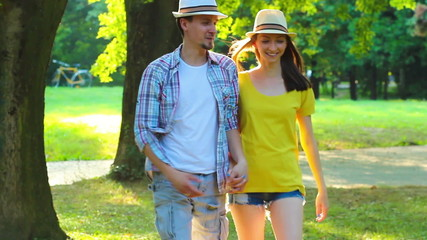 Romantic young couple walking in park.