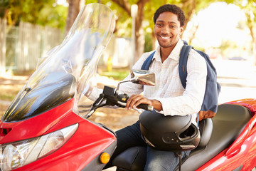 Young Man Riding Motor Scooter To Work