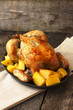 chicken baked with potatoes  on a wooden background