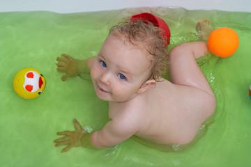 Smiling baby girl taking bath
