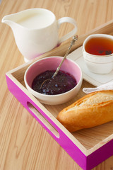 tray with breakfast: baguette, jam and tea