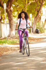 Young Woman Cycling Along Street To Work