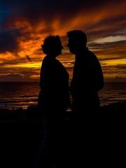 Liebespaar bei Sonnenuntergang blickt sich tief in die Augen