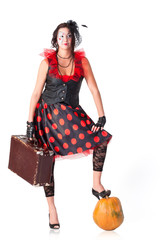 Beautiful woman with suitcase and pumpkin
