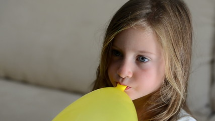 Girl inflating a yellow balloon
