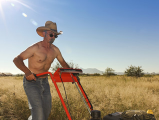 A Shirtless Cowboy Operates a Brush Mower on the Ranch