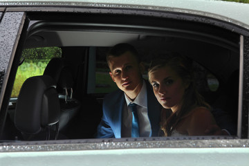 Wedding day in rainy weather, couple sitting in the car.