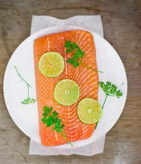 fresh, crude fillet of a salmon with slices of a lime and greens