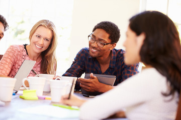Group Of Business People Sitting Around Table In Meeting