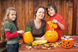 Kids carving jack-o-lanterns for Halloween