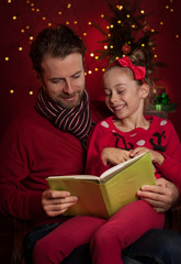 Christmas - smiling father and daughter reading a book