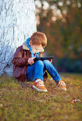 happy stylish boy playing on media tablet in city park