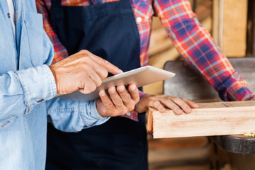 Male And Female Carpenters Using Digital Tablet