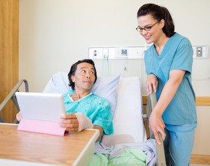 Nurse And Male Patient Using Digital Tablet