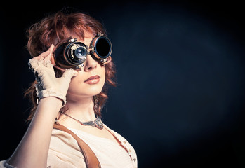 Redhair steampunk woman with goggles