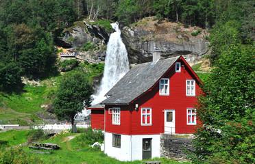 steinsdalsfossen, rotes holzhaus und wasserfall in norwegen