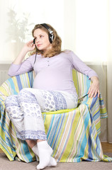 Young pregnant woman listening to music on headphones at home