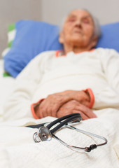 elderly woman lying ill in her bed with a stehoscope , black and