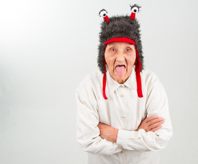 grandma in funny hat showing her tongue