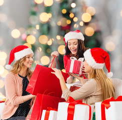 smiling young women in santa hats with gifts