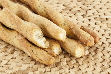 Breadsticks on a wicker mat, narrow focus