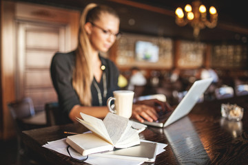Business woman in glasses, coffee and laptop in restaurant