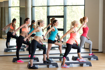 group of women with dumbbells and steppers