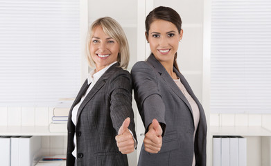 Portrait: Successful business woman team making thumbs up gestur