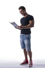 Full body shot of handsome man reading book on white